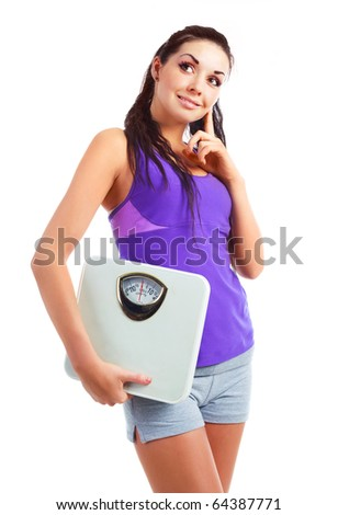 beautiful young woman wearing sports clothes holding scales - stock photo