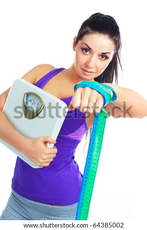 beautiful young woman wearing sports clothes holding scales and a measuring tape