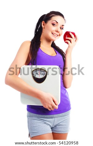 beautiful young woman wearing sports clothes holding scales and eating an apple
