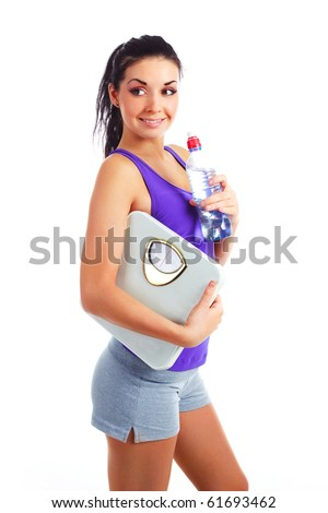 beautiful young woman wearing sports clothes holding scales and holding a bottle of water - stock photo