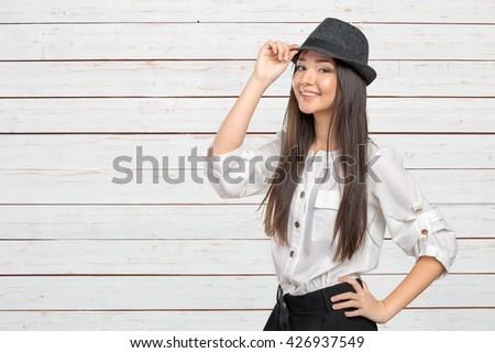 Beautiful young woman wearing summer fedora straw hat posing - stock photo