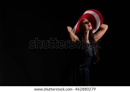 Beautiful young woman wearing summer hat with large brim over dark background
