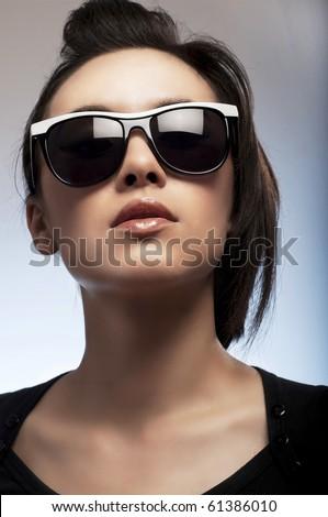 Beautiful young woman wearing sunglasses - stock photo