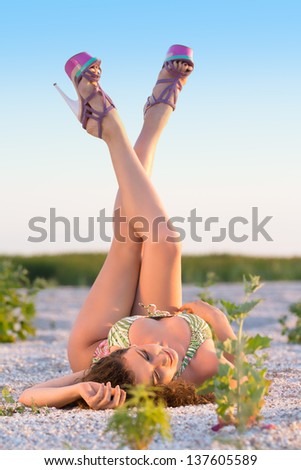 Beautiful young woman wearing trendy heels posing with raised legs - stock photo
