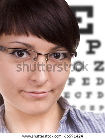 Beautiful young woman wears trendy glasses. Eye chart in background.