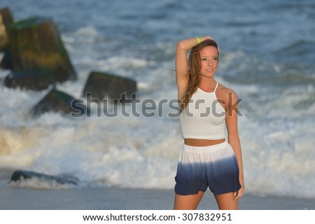 Beautiful young woman white tank top and blue & white shorts poses in the sunset on the beach as waves crash behind her - stock photo