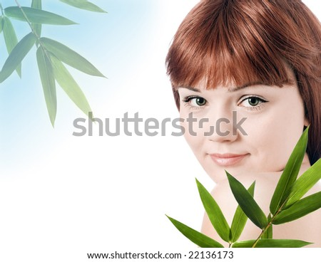 Beautiful young woman with a bamboo plant - stock photo