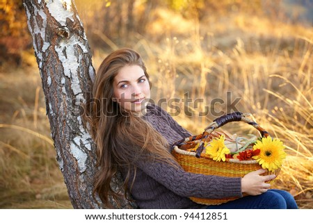 Beautiful young woman with a basket of flowers sitting at the shade of a tree in autumn. - stock photo