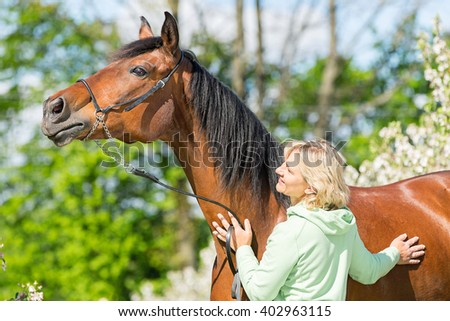 Beautiful young woman with a bay horse. - stock photo