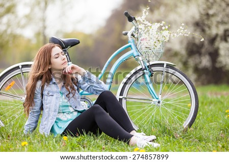 Beautiful young woman with a bike in park - rest after a long trip - stock photo