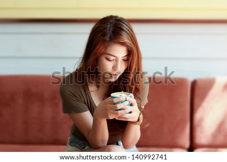 Beautiful young woman with a cup of  a cafe - stock photo