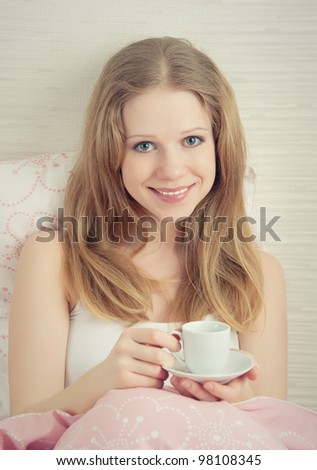 beautiful young woman with a cup of morning coffee in bed