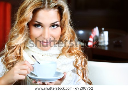 Beautiful young woman with a cup of tea at a caf - stock photo