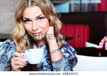 Beautiful young woman with a cup of tea at a cafe. - stock photo