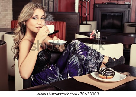 Beautiful young woman with a cup of tea at a cafe - stock photo