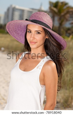 Beautiful young woman with a fancy purple hat in Miami's South Beach. - stock photo