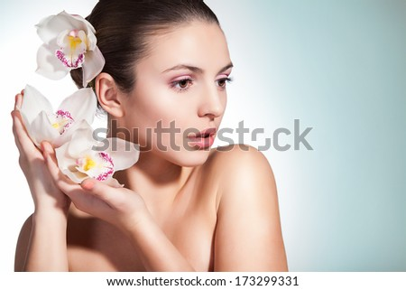 Beautiful young woman with a flower in her hair against a blue background