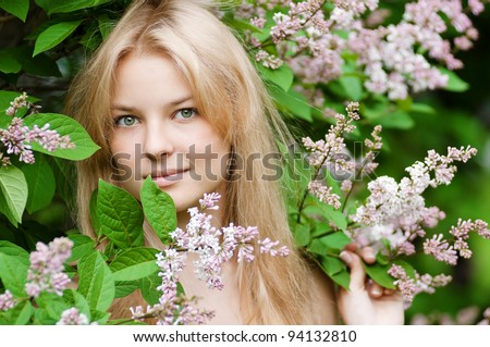 Beautiful young woman with a flower lilac over face - stock photo