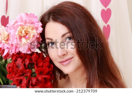 Beautiful young woman with a gentle smile, holding a bouquet of flowers