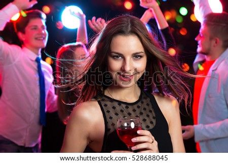 Beautiful young woman with a glass of wine at a party