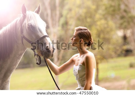 beautiful young woman with a grey horse in the country - stock photo