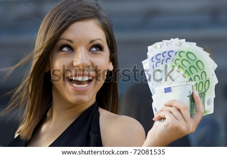 Beautiful young woman with a handful of Euro bills.