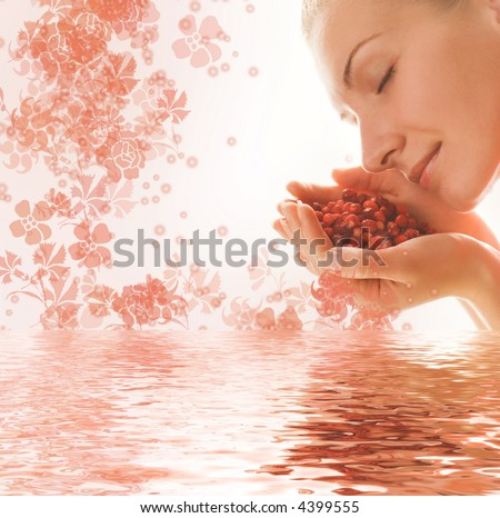 Beautiful young woman with a hanful of aromatic berries reflected in rendered water - stock photo