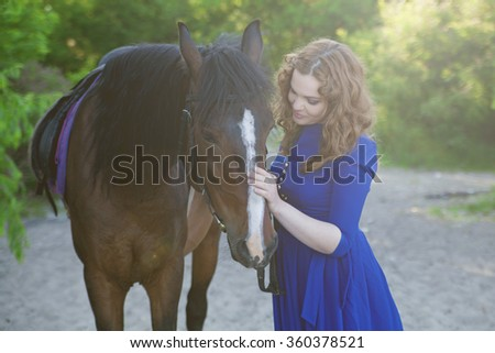 Beautiful young woman with a horse - stock photo