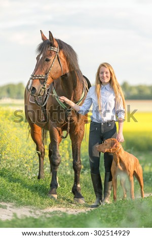 Beautiful young woman with a horse and a dog. - stock photo