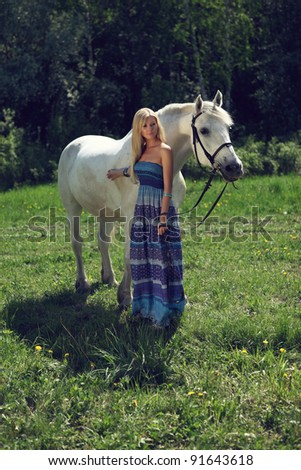 beautiful young woman with a horse in the forest - stock photo