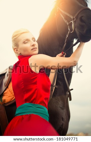Beautiful young woman with a horse outdoor in sunset, sunrise - stock photo