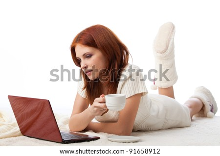 Beautiful young woman with a laptop lies on warm plaid on a white background.