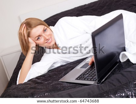beautiful young woman with a laptop on the bed at home