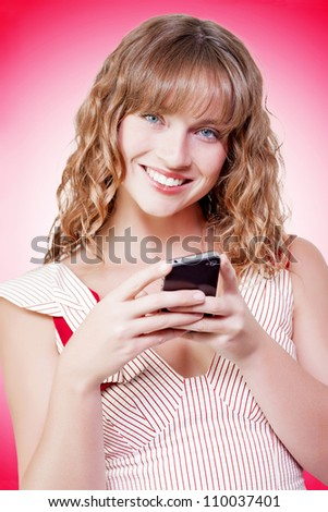 Beautiful young woman with a lovely gentle smile texting on her mobile phone against a red studio background with gradient colour - stock photo