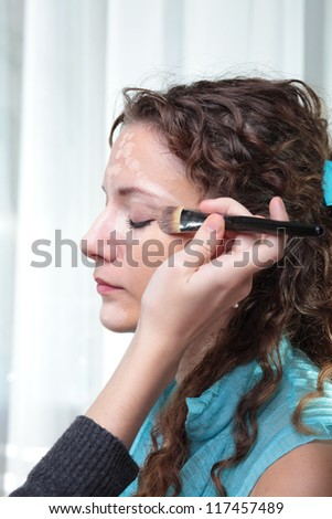 Beautiful young woman with a make-up brush. - stock photo