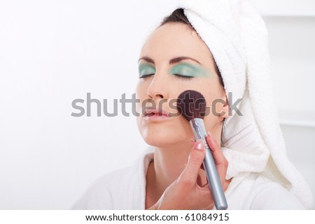 Beautiful young woman with a make-up brush - stock photo
