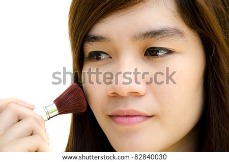 Beautiful young woman with a make-up brush, isolated on white background. - stock photo