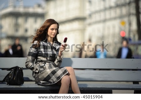 beautiful young woman with a mobile phone with city life on background - stock photo