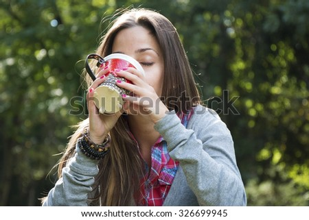 Beautiful young woman with a red cup drinking coffee in a morning park