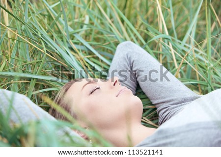 Beautiful young woman with a serene expression lying on her back sleeping in the grass enjoying the outdoor peace and tranquillity