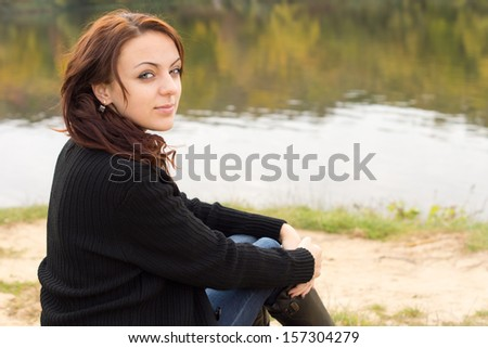 Beautiful young woman with a serene smile sitting alongside the calm water of a river or lake turning to look at the camera - stock photo