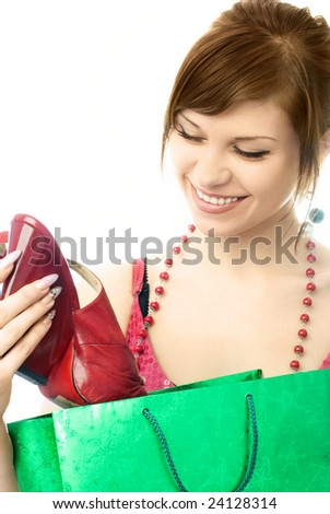 beautiful young woman with a shopping bag looking at the shoes she has just bought - stock photo