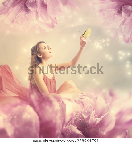 Beautiful young woman with a small butterfly on peony flower - stock photo