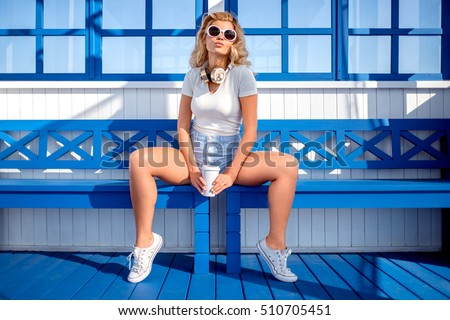 Beautiful young woman with a take away coffee cup, sitting on the bench and waiting for a water taxi at the station.