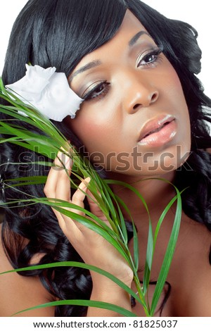Beautiful young woman with a tropical flower in her hair and palm leaves, close-up shot - stock photo