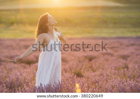 Beautiful young woman with a white dress and a straw hat standing in the middle of a lavender field at in the golden light of the sunset praising the beauty of life. - stock photo