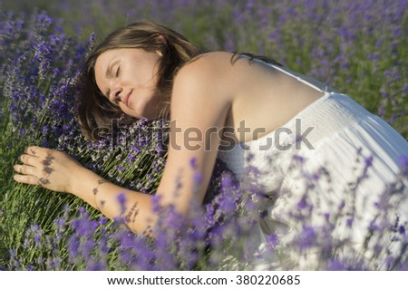 Beautiful young woman with a white dress hugging a lavender bush enjoying the fragrance. - stock photo