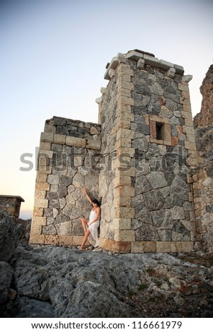 beautiful young woman with a white dress posing on old stone lighthouse - stock photo