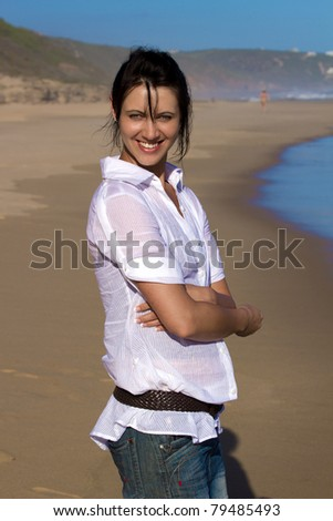 Beautiful young woman with a white shirt standing on the beach and smiling - stock photo