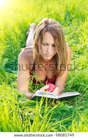 Beautiful young woman with an apple in hand lying on the green grass and reading a book a sunny day against a background of green nature